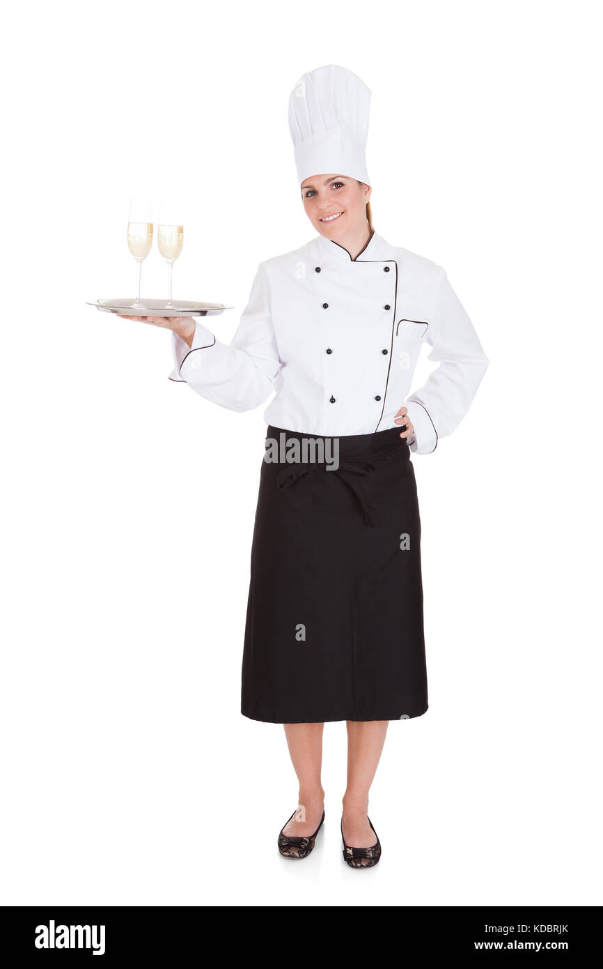 Portrait Of Female Chef Holding Champagne Over White Background - Stock Image