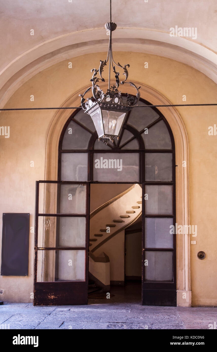 Entrance to Italian flats Curved stairwell in sight, peach pale stone work, large antique lantern light fitting - Stock Image