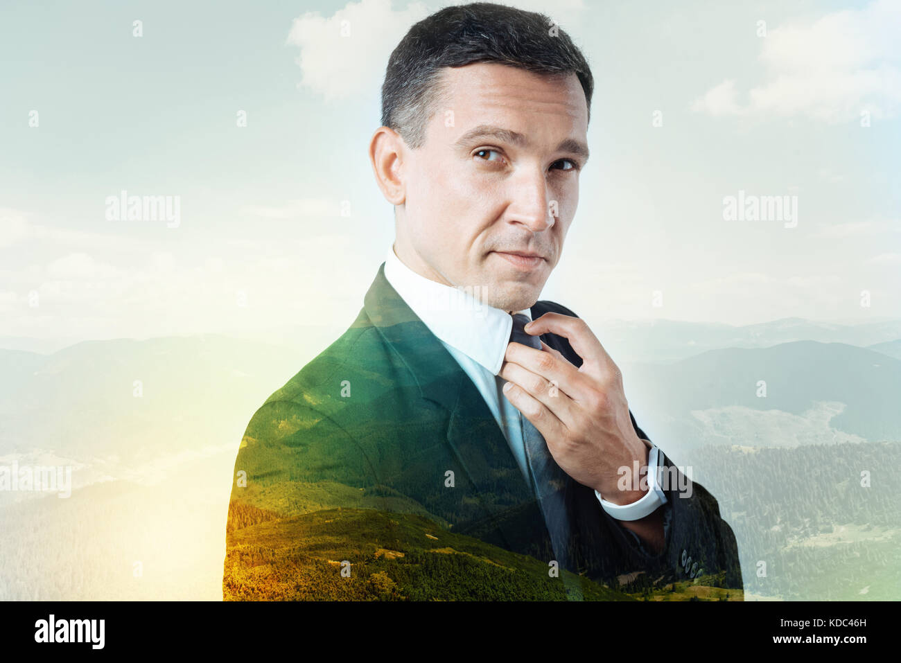 Handsome young man fixing his stylish tie - Stock Image