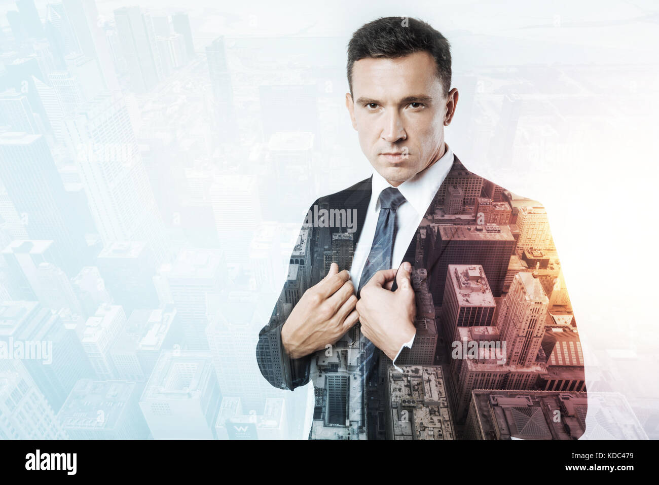 Elegant man in a black suit standing and frowning - Stock Image