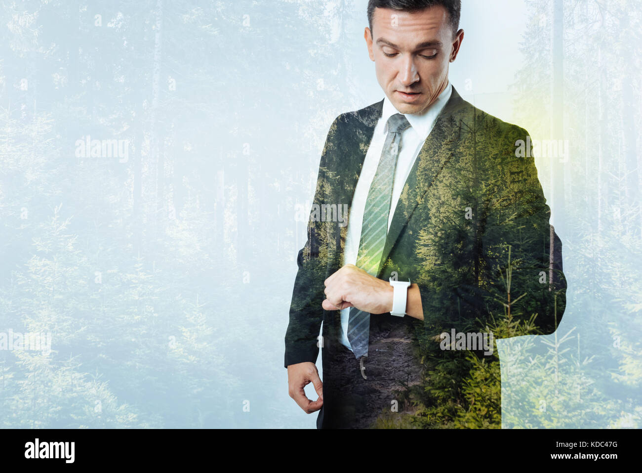 Elegant man checking time with a smart watch on his wrist - Stock Image