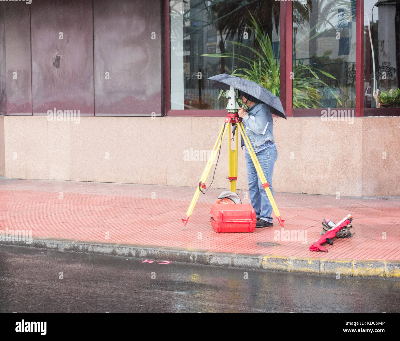 Female surveyor working in the rain in Spain - Stock Image