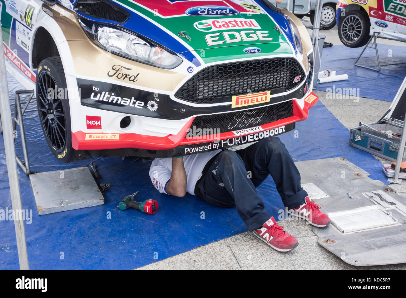 Rally mechanic under car at Gran Canaria rally. - Stock Image