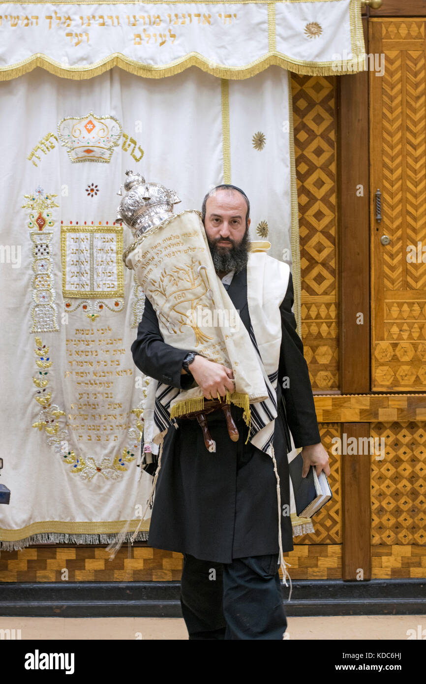 A religious Jewish man carrying a Torah scroll from the Holy Ark to the place where it will be read. In Brooklyn, - Stock Image