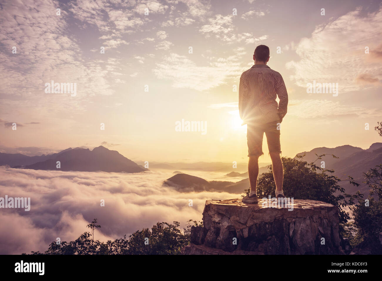 Man on a summit above the clouds - Stock Image