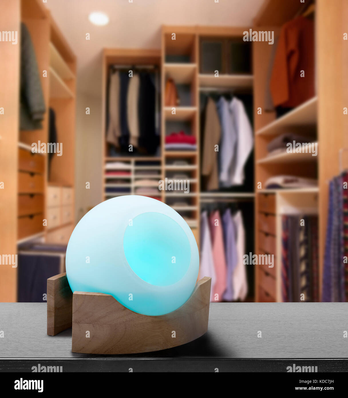 Colored air freshener in glass container in modern dressing room - Stock Image