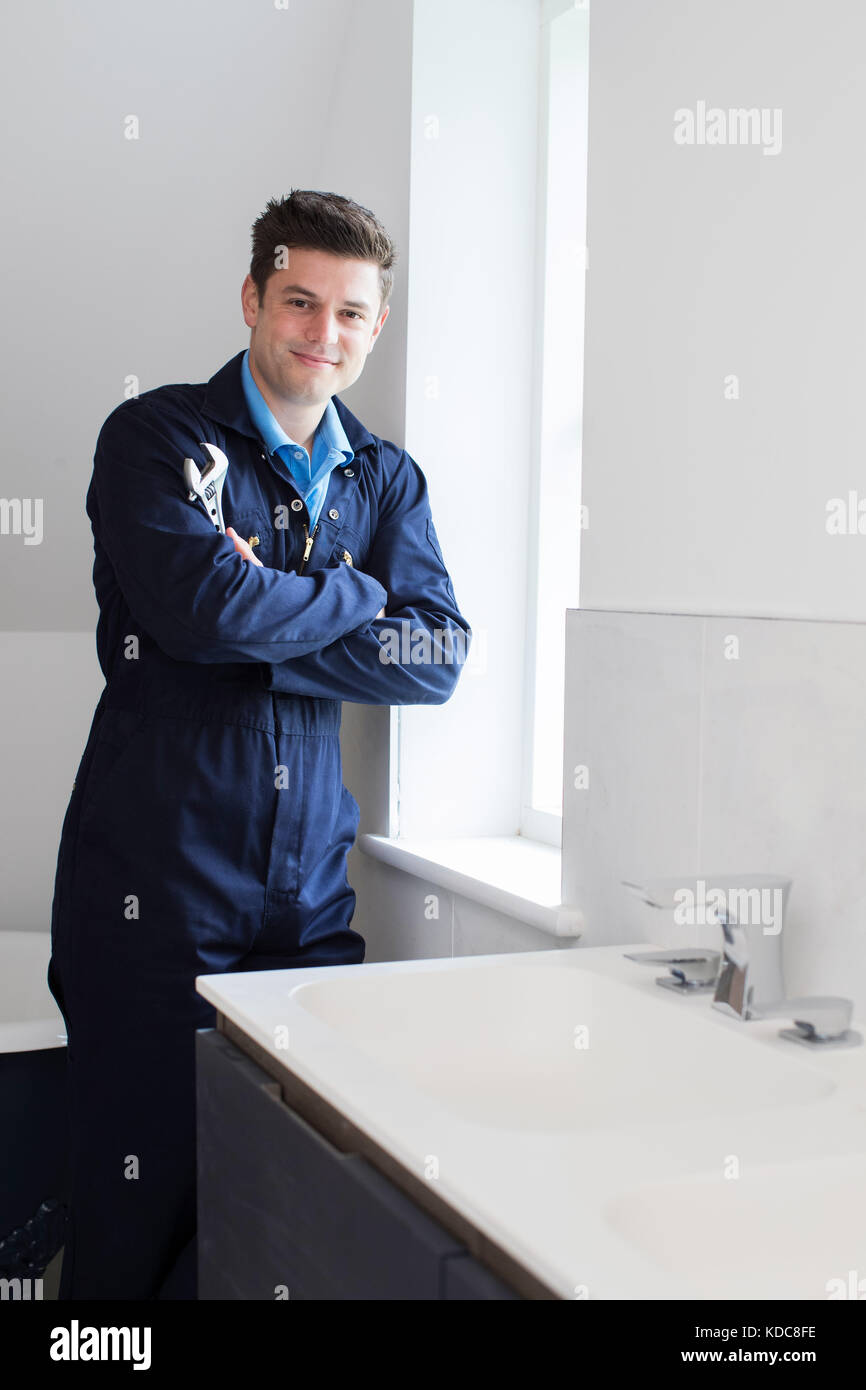 Portrait Of Plumber Standing By Sink In Bathroom - Stock Image