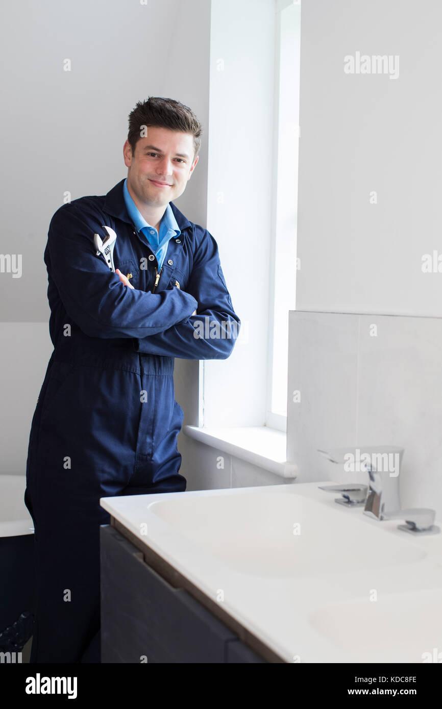 Portrait Of Plumber Standing By Sink In Bathroom - Stock Image