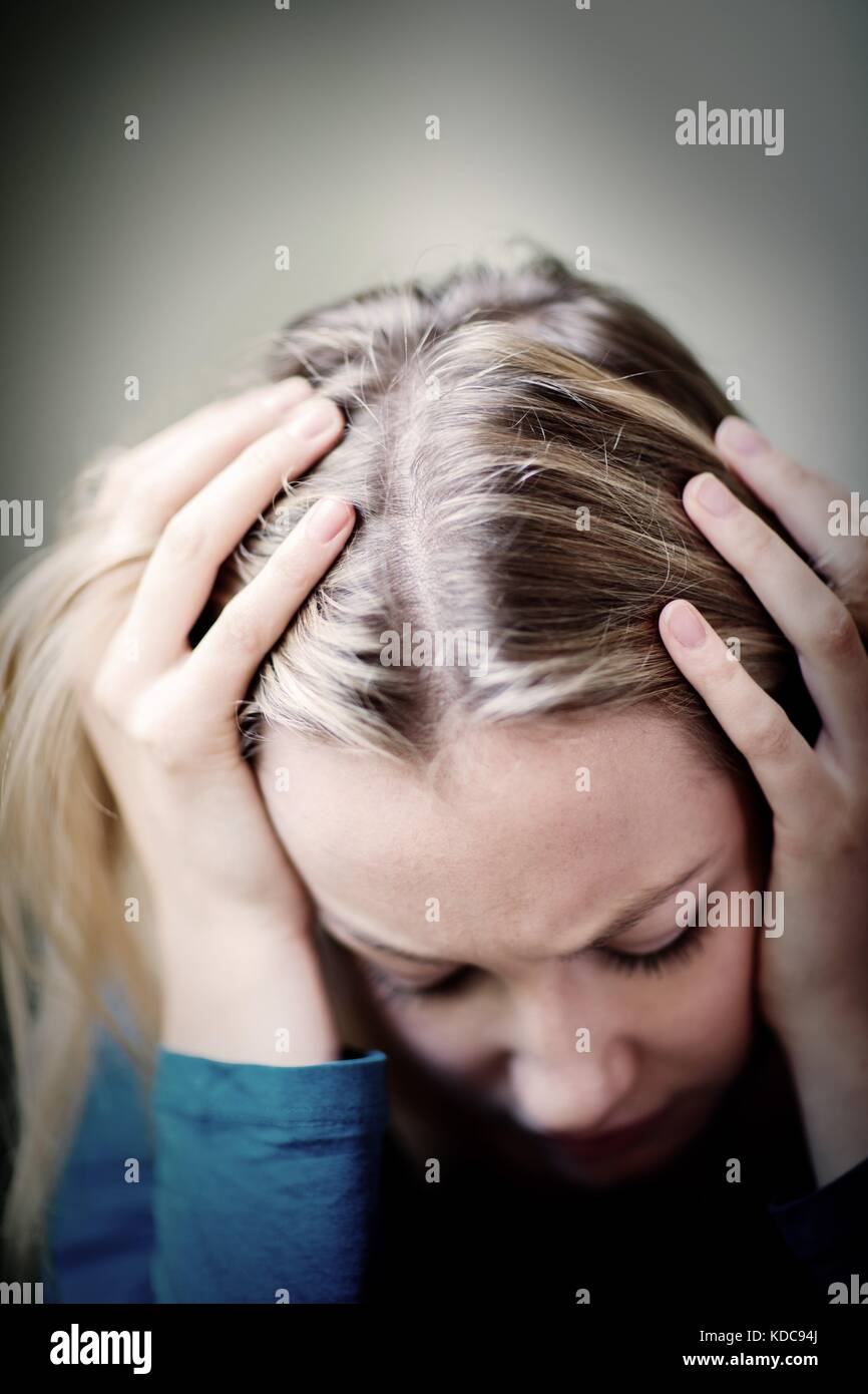 Young Woman Suffering From Depression With Head In Hands - Stock Image