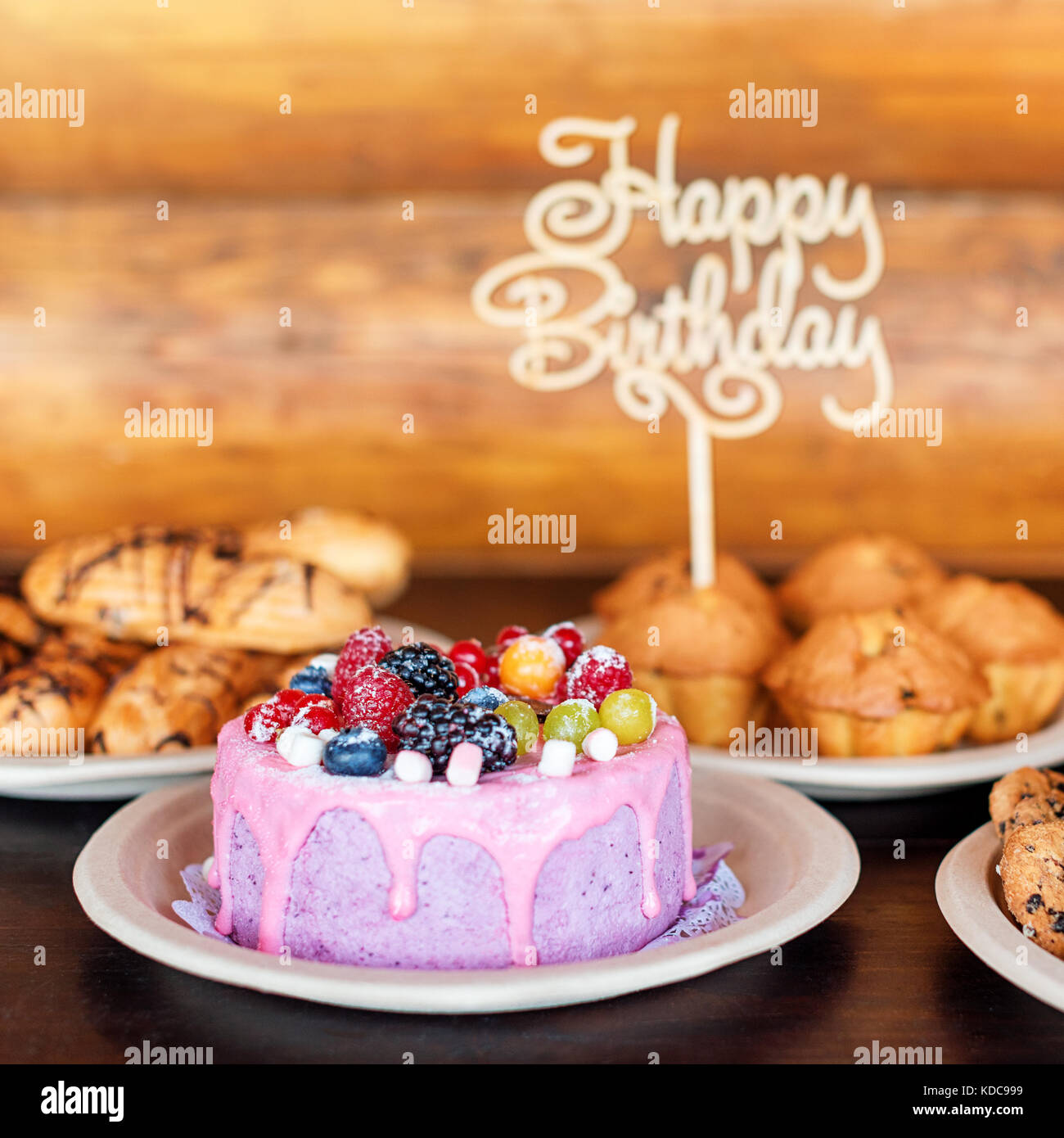 Birthday cake and muffins with wooden greeting sign on rustic background. Wooden sing with letters Happy Birthday - Stock Image