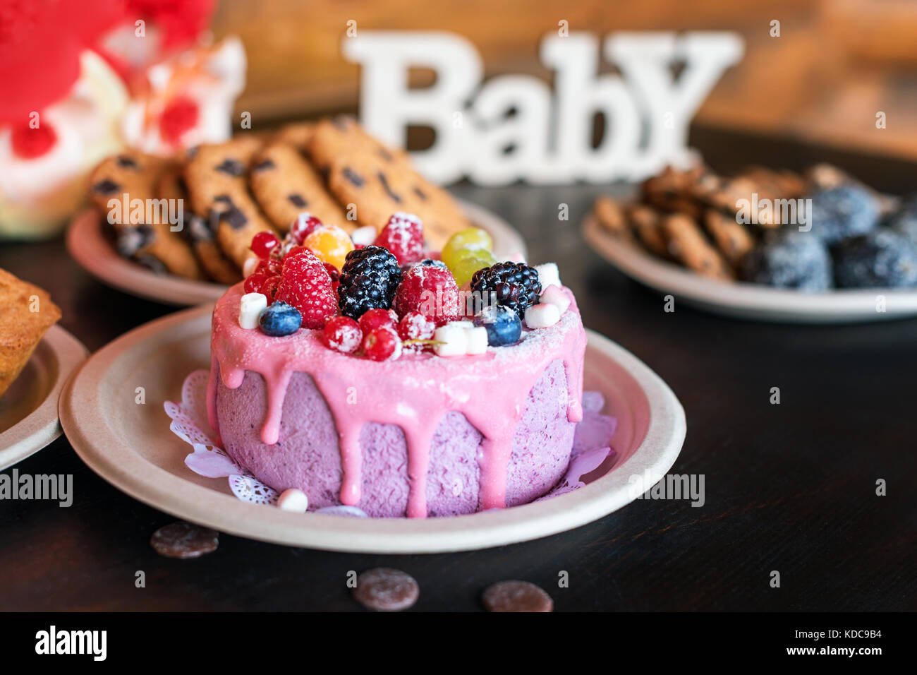 Birthday cakes and muffins with wooden greeting signs on rustic background. Wooden sing Baby and holiday sweets. - Stock Image