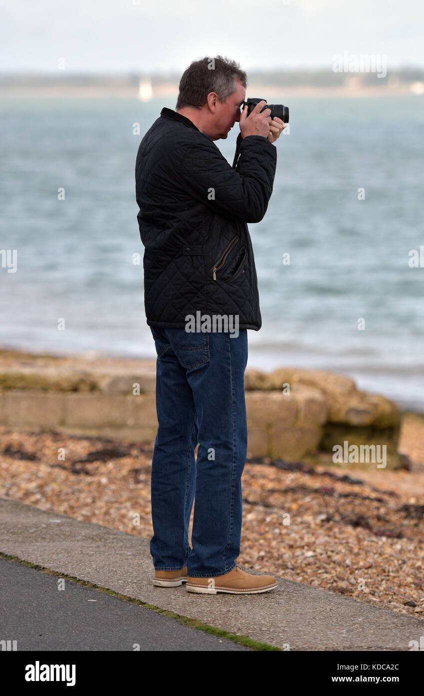 a man standing on the sea front or promenade esplanade looking through the viewfinder of a camera taking a picture - Stock Image