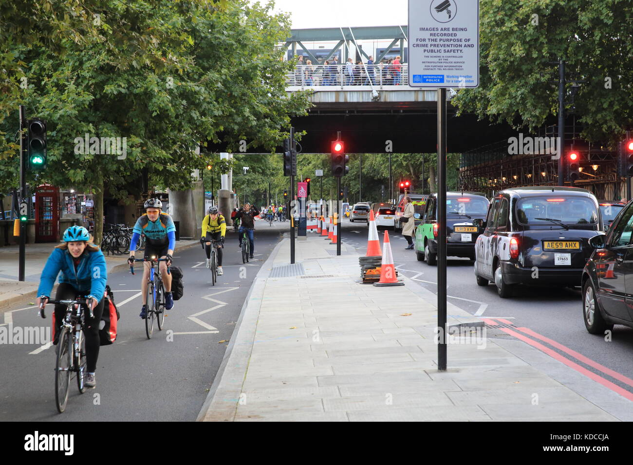Cyclists in a segregated lane, and traffic on the Embankment in London, England, UK - Stock Image