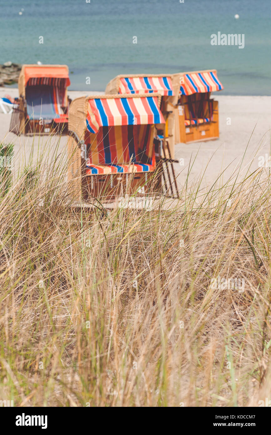 Colorfuled striped roofed chairs on sandy beach in Travemunde., Lubeck, Germany - Stock Image