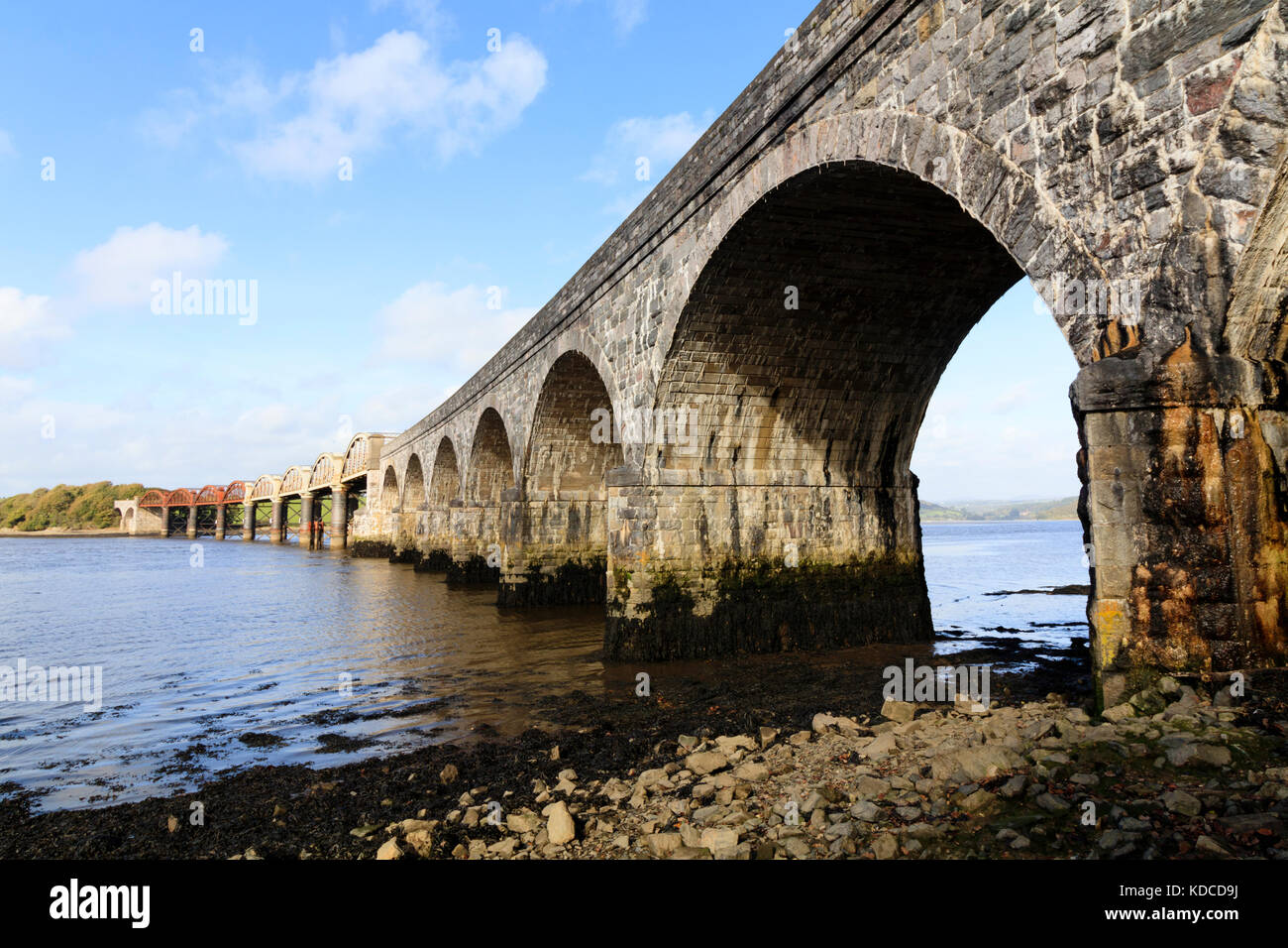 Stone and metal arches of the rail bridge that carries the Tamar Line over the tidal water of the River Tavy estuary Stock Photo
