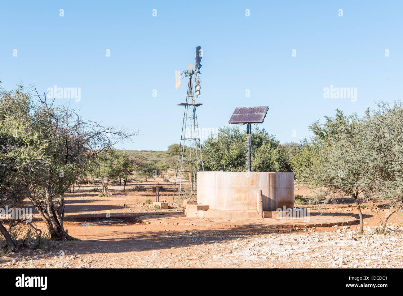 A water-pumping windmill and solar panels for a waterpump near Schmidtsfrift, a village in the Northern Cape Province - Stock Image