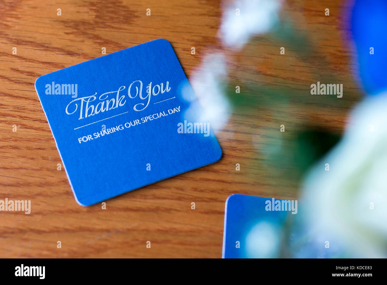 Blue celebration beer mat with silver text on a wooden table at the reception of a renewal of vows stating 'Thank - Stock Image
