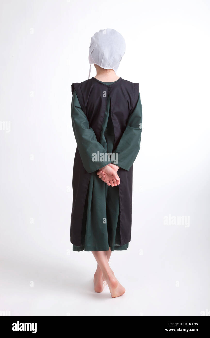 A young barefoot Amish girl in a green and black outfit isolated on a background Stock Photo