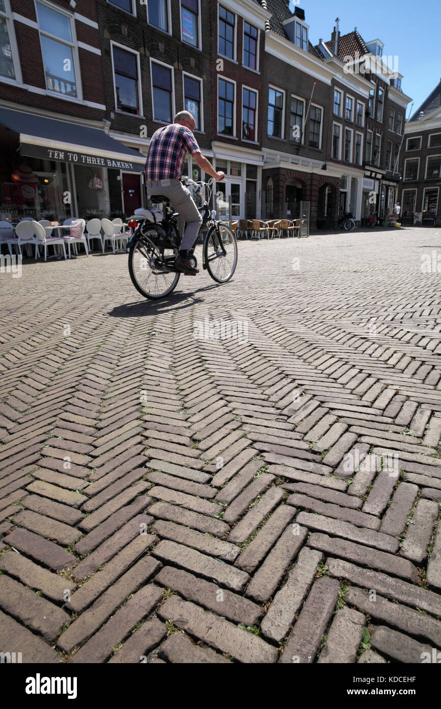 Red brick paving with a herringbone pattern in Delft's pedestrianised Market Square. - Stock Image