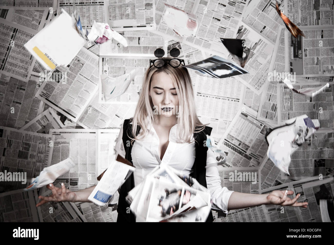 Young blonde in a sunglasses surrounded with newspapers - Stock Image