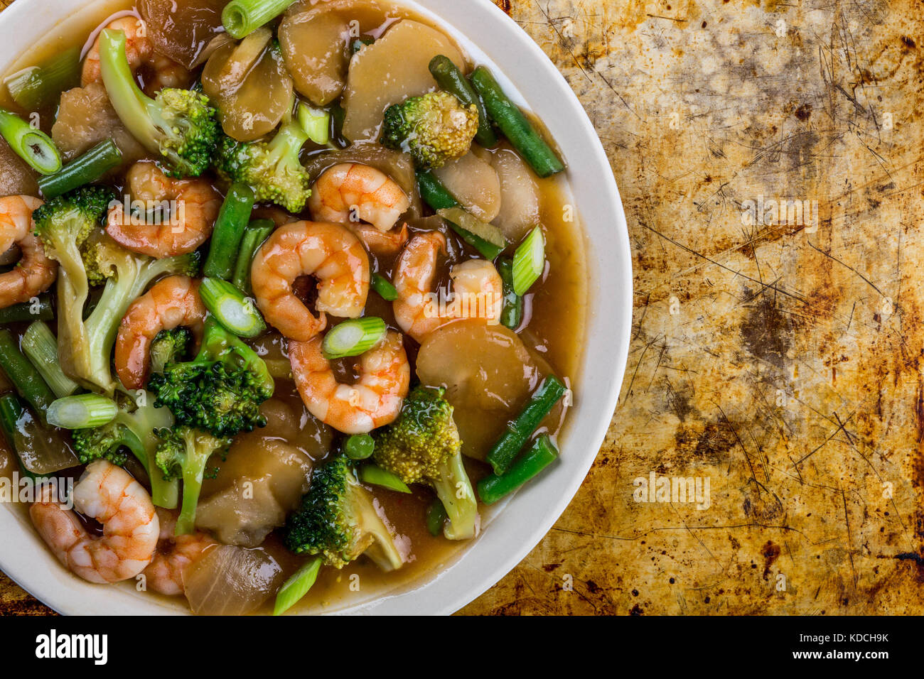 Chinese Style Stir Fried King Prawn With Ginger and Spring Onions On A Distressed Oven or Baking Tray - Stock Image