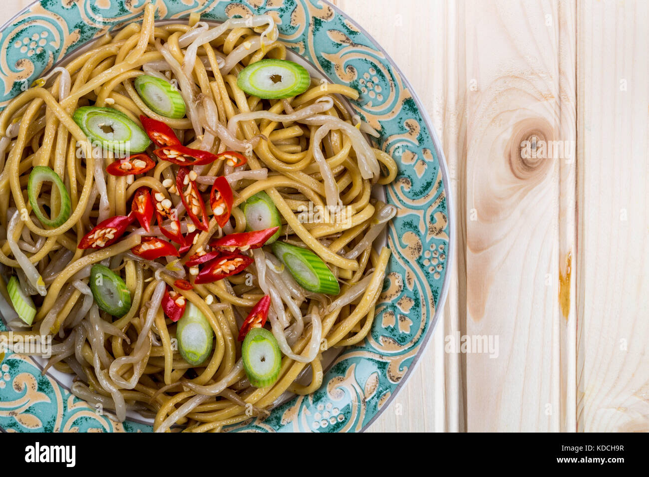 Chinese Style Wok Stir Fried Egg Noodles with Beansprouts and Red Chilli On A Light Pinewood Background, - Stock Image