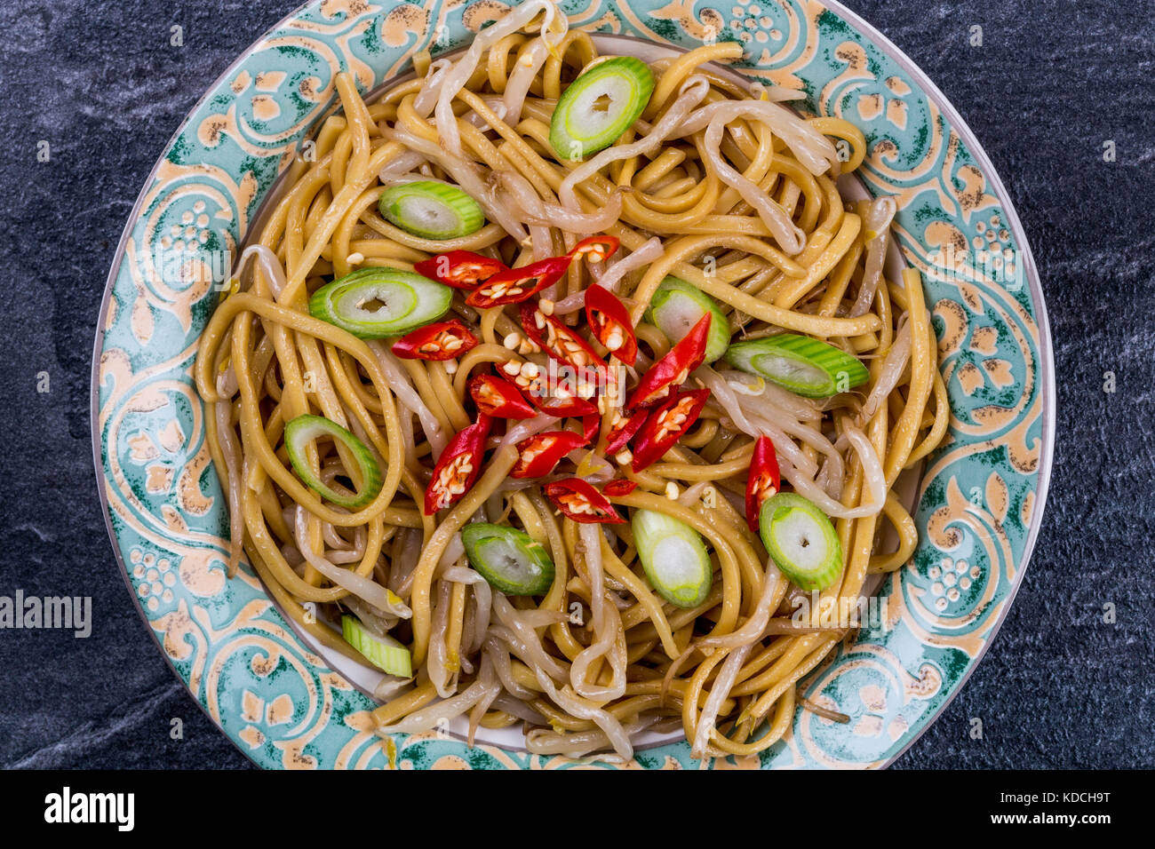 Chinese Style Wok Stir Fried Egg Noodles with Beansprouts and Red Chilli On A Black Slate Kitchen Tile - Stock Image