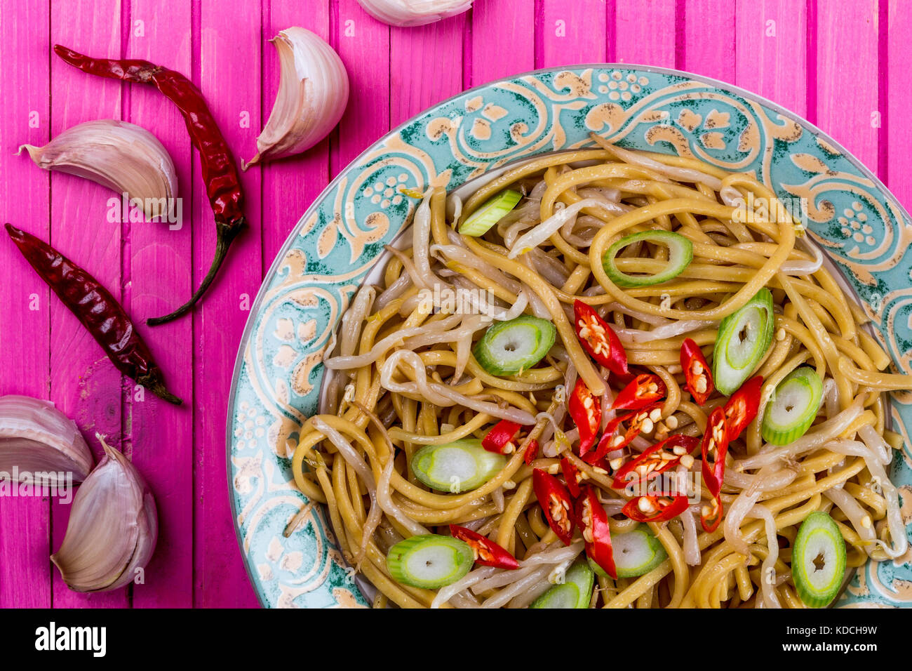 Chinese Style Wok Stir Fried Egg Noodles with Beansprouts and Red Chilli On A Pink Wooden Background - Stock Image