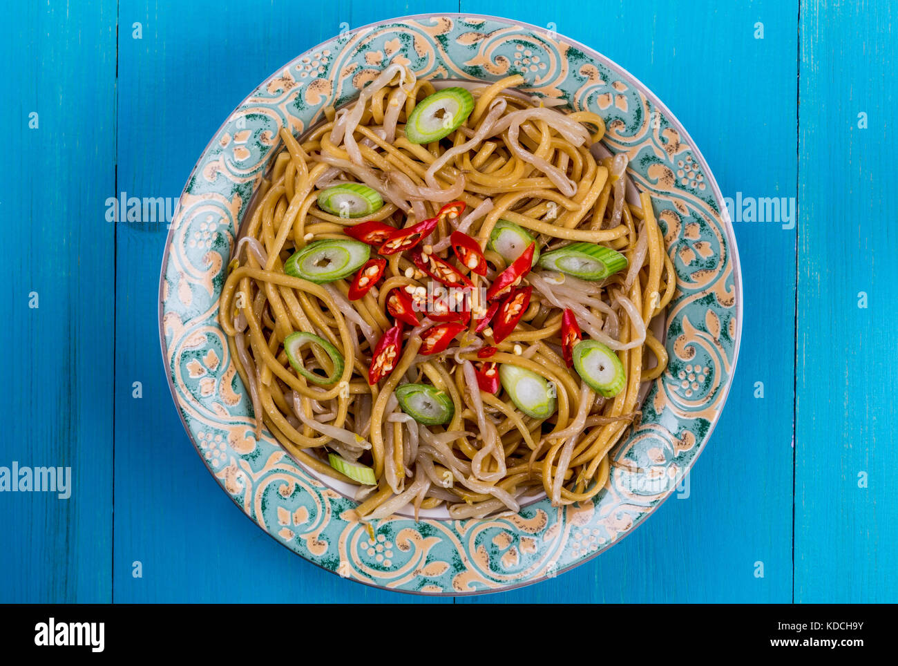 Chinese Style Wok Stir Fried Egg Noodles with Beansprouts and Red Chilli On A Blue Wooden Background - Stock Image