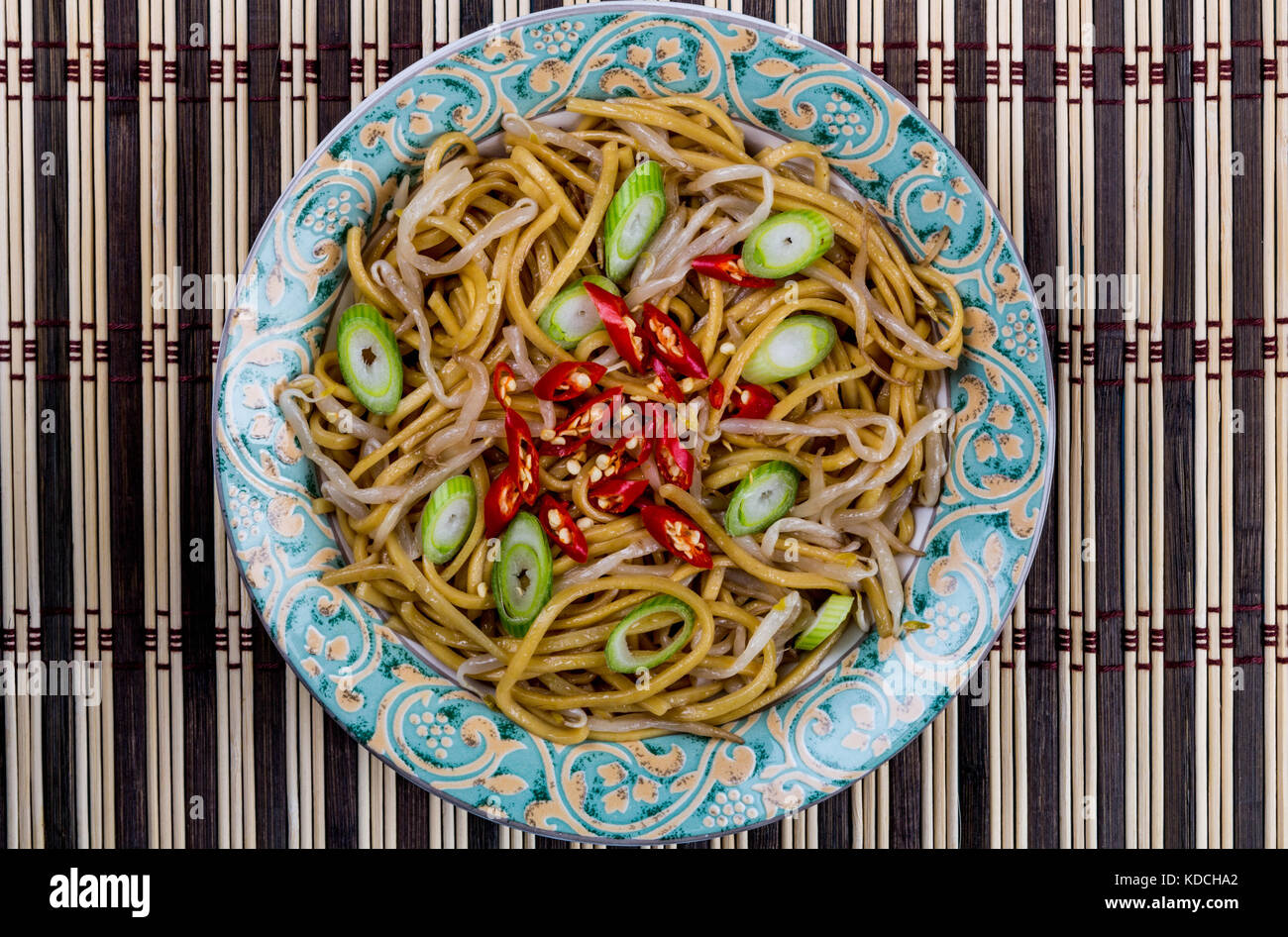 Chinese Style Wok Stir Fried Egg Noodles with Beansprouts and Red Chilli On A Bamboo Table Mat - Stock Image