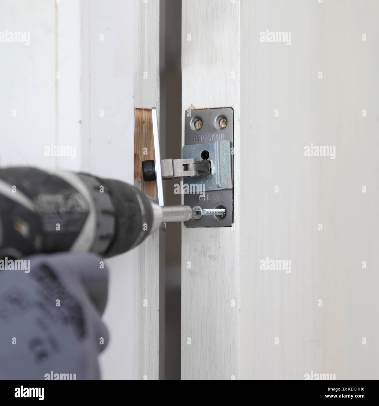 A workman installs a concealed closer to a new fire door as part of the refurbishment of a residential block in - Stock Image