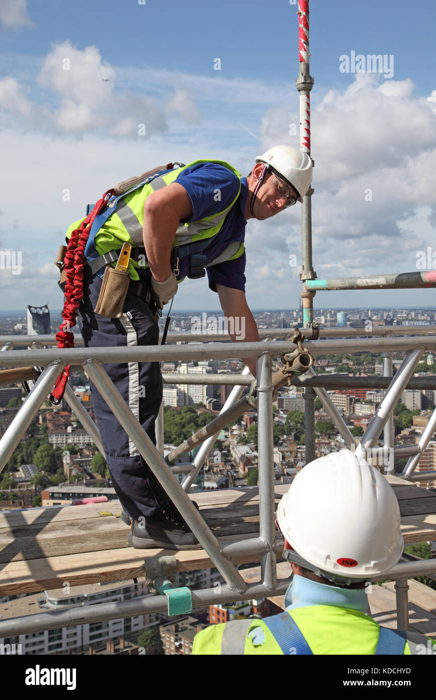 Two scaffolding erectors assemble a temporary work platform on a tower block high above London - Stock Image