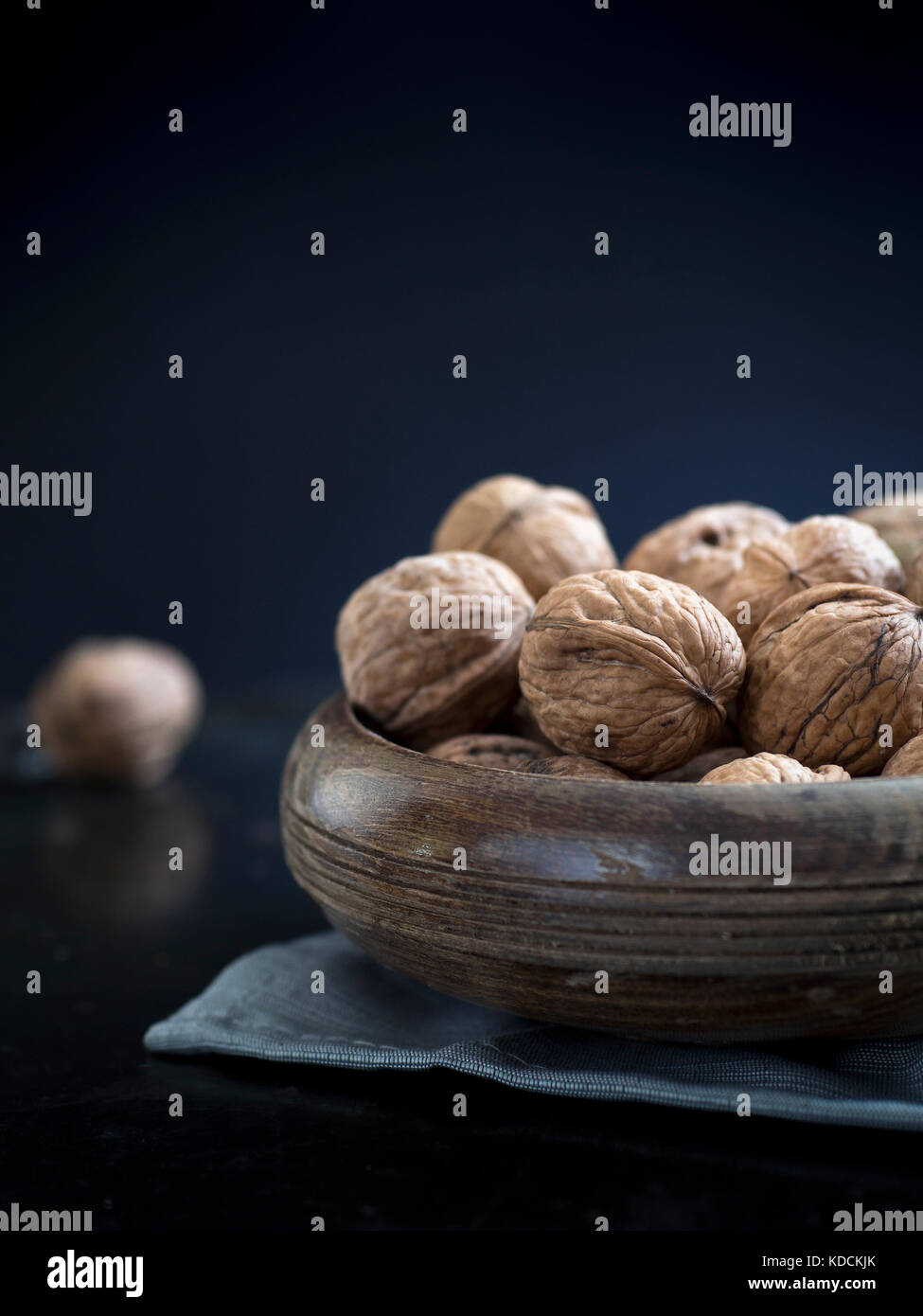 Walnuts in a bowl on a dark background - Stock Image