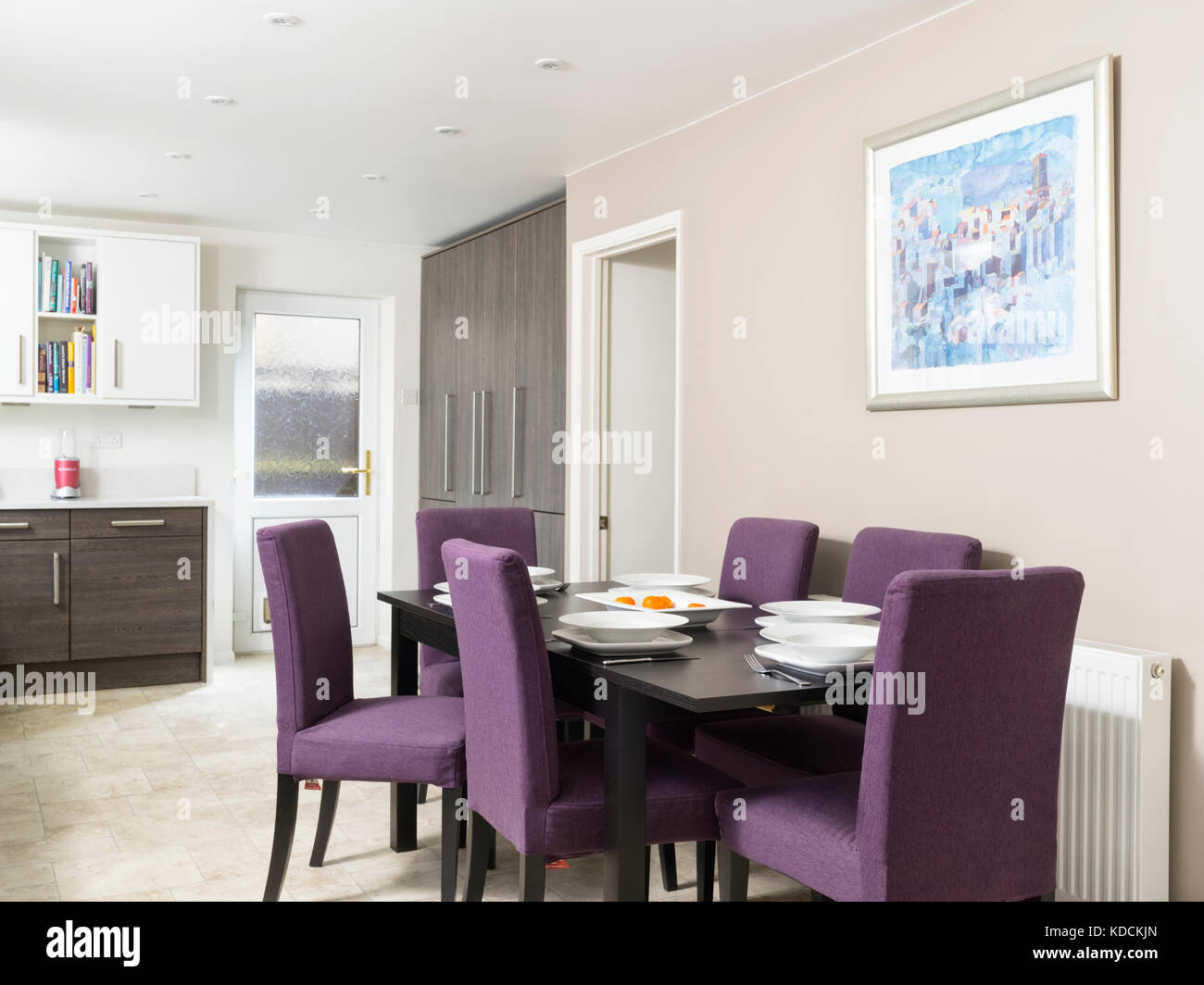 A dark wood dinning table with purple chairs, set for a meal in the contemporary kitchen diner of a modern UK home. Stock Photo