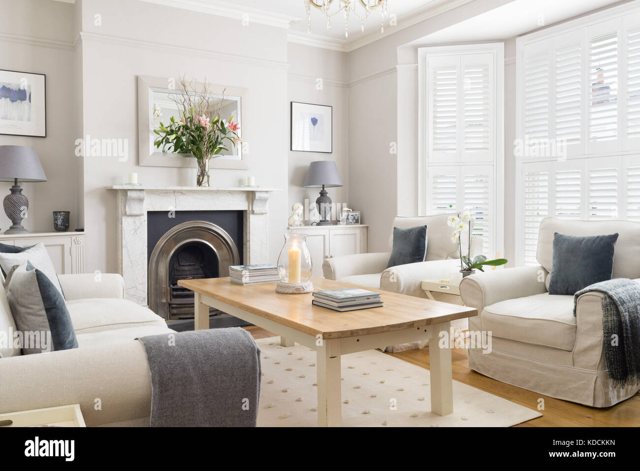 A bright, cotemporary living room space in a Victorian home with comfortable modern furniture, shuttered windows - Stock Image