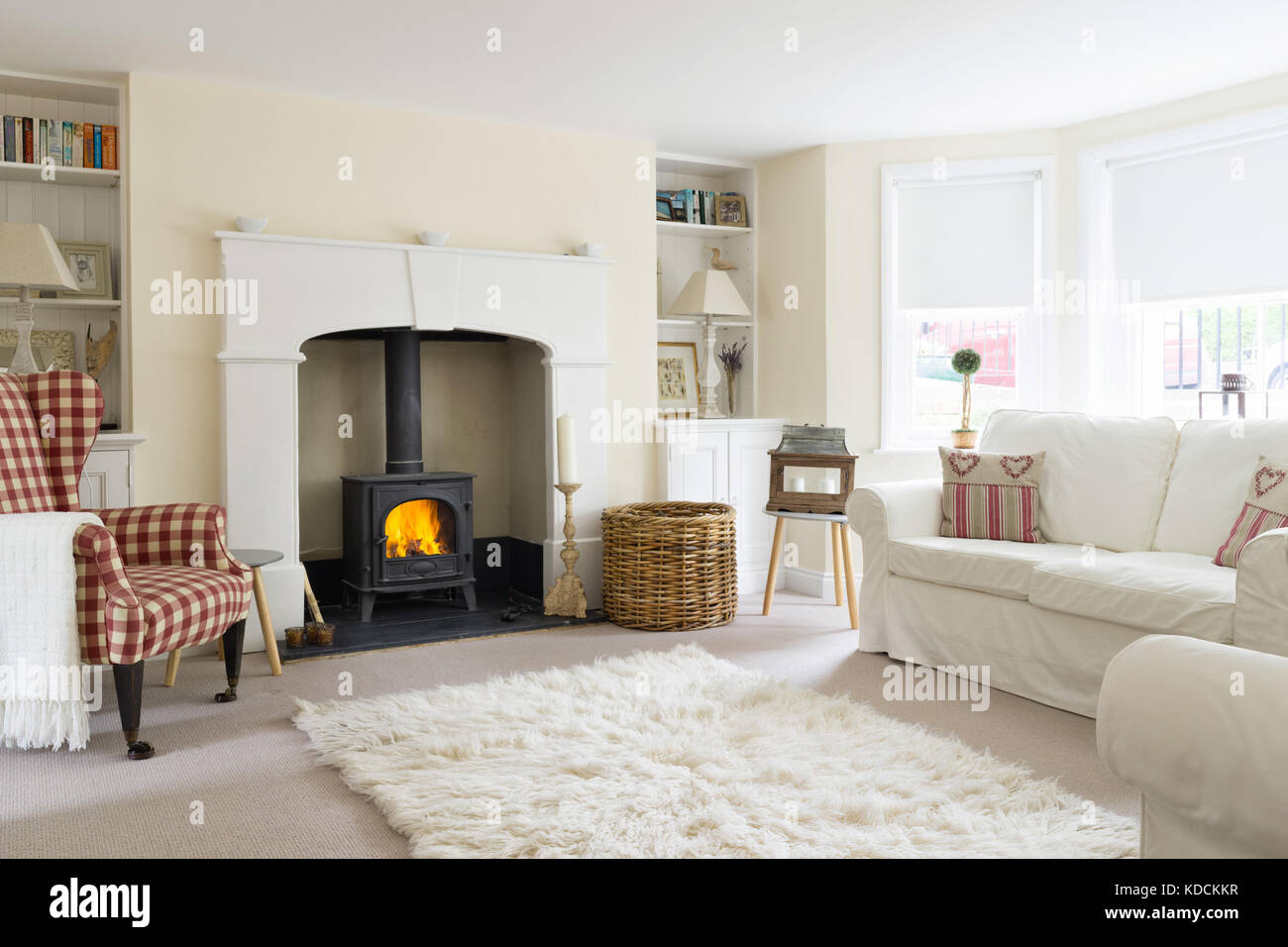 A basement, converted in to a comfortable living room. With shuttered windows, wood burning stove and contemporary - Stock Image