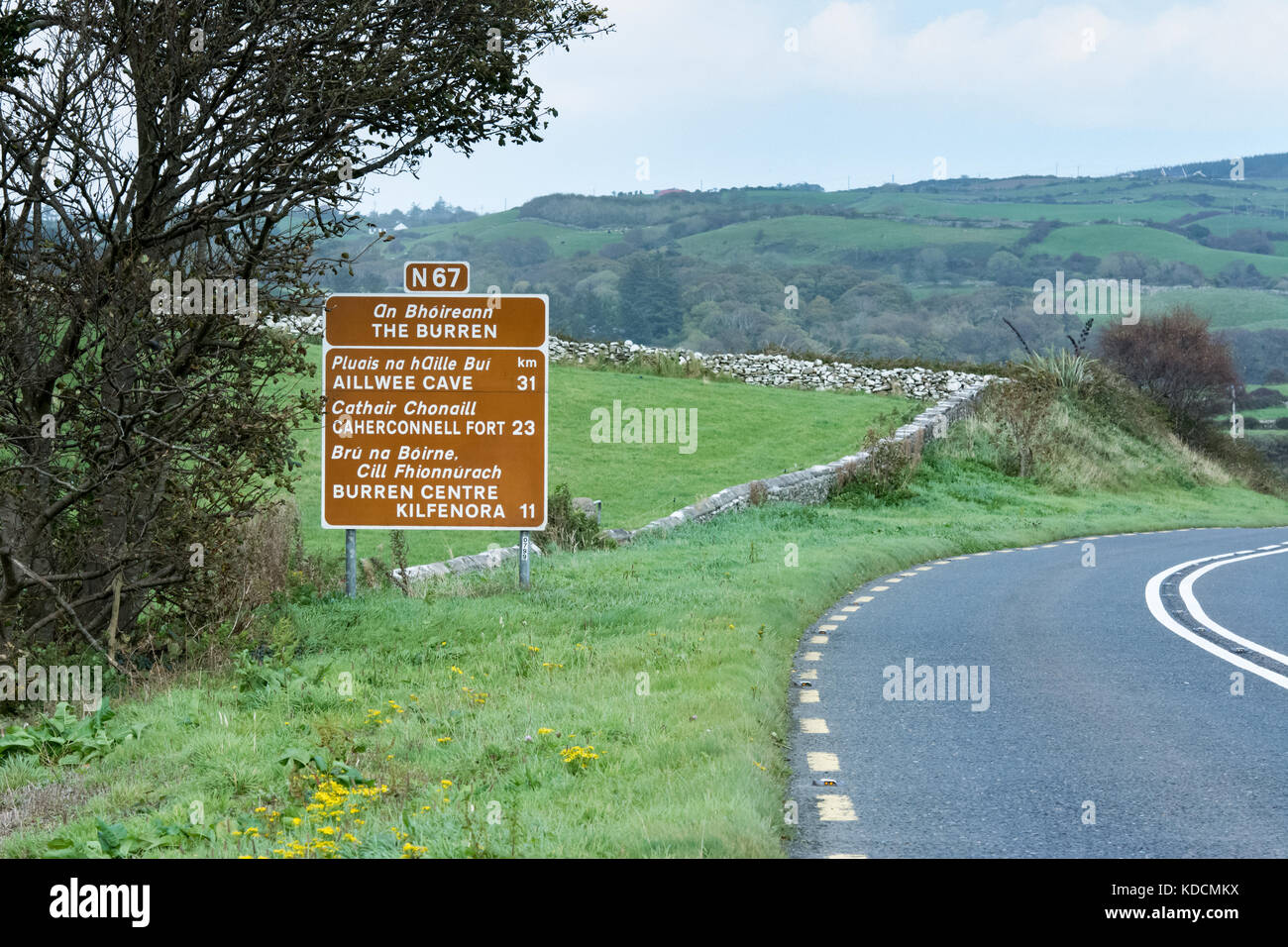 Road through the Burren (County Clare, Ireland) with signpost for various tourist locations. - Stock Image
