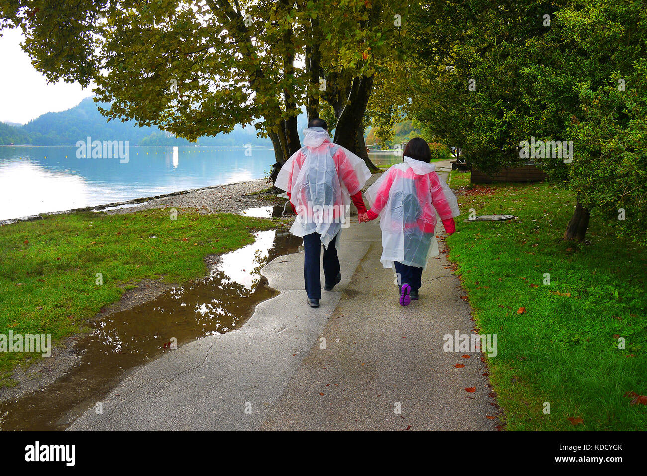 A couple in fold-up raincoats walk beside Lake Bled in Bled, Slovenia. - Stock Image