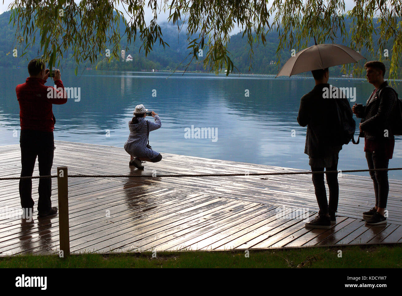 Tourists taking photographs beside Lake Bled in Bled, Slovenia. - Stock Image