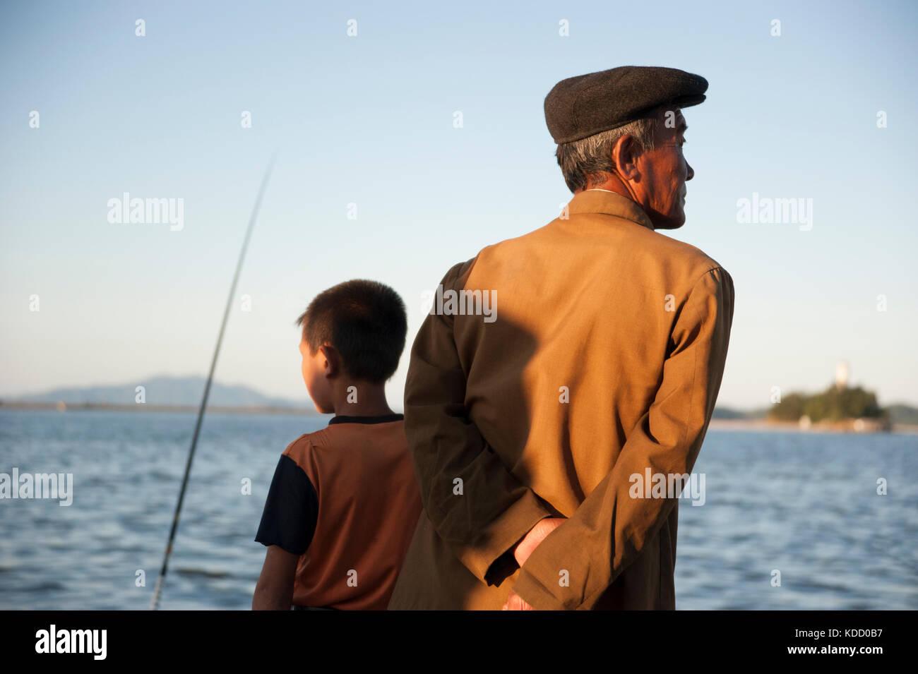 Les enfants sont toujours au rendez-vous lorsque les pêcheurs viennent en fin d'après midi le long du port de Wonsan. Stock Photo