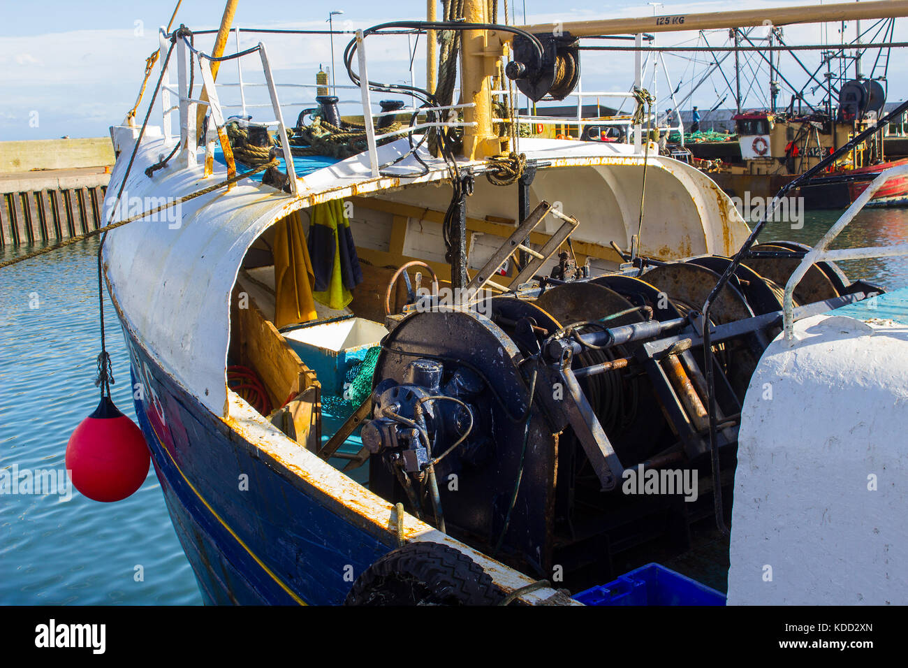 The covered bow and heavy duty winches and cables on the deck of a commercial fishing trawler - Stock Image