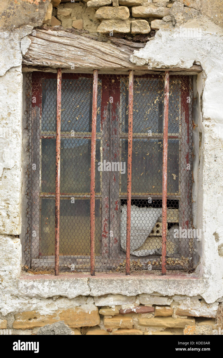 a barred window with cracked plaster and broken glass showing neglect and dilapidation in a shabby chic kind of - Stock Image