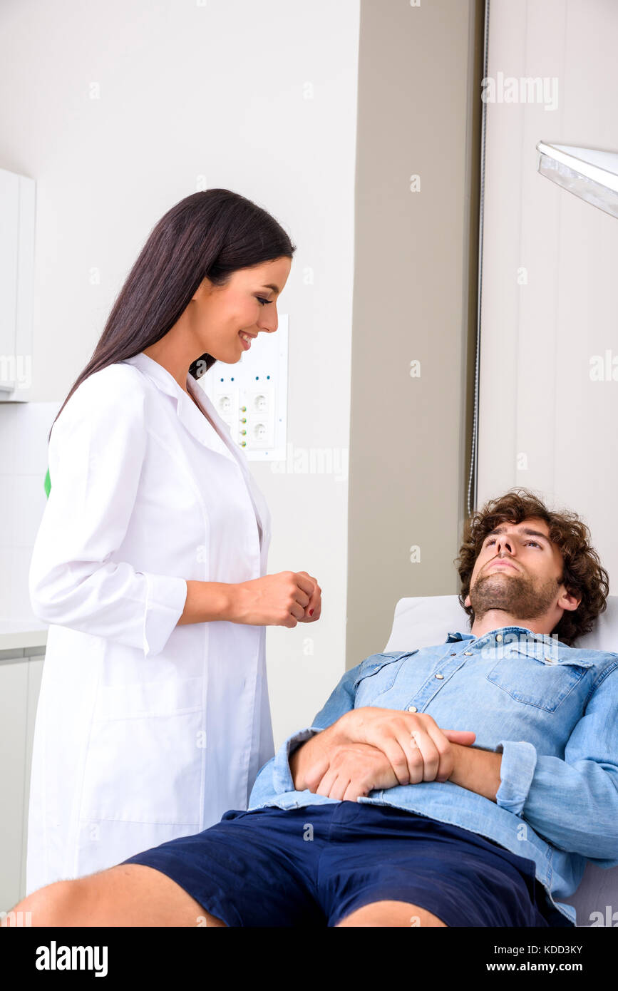 A young male patient in the emergency room getting attended by a female professional physician. Stock Photo