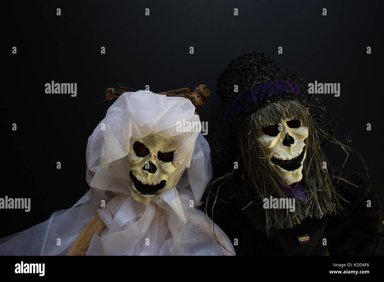 Close up of skeleton bride and groom in white and black,  against a black background. - Stock Image
