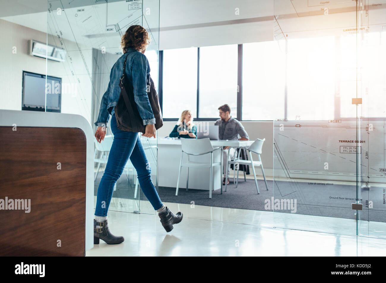 Female client moving forward towards conference room for meeting with designers. Creative office with executives - Stock Image