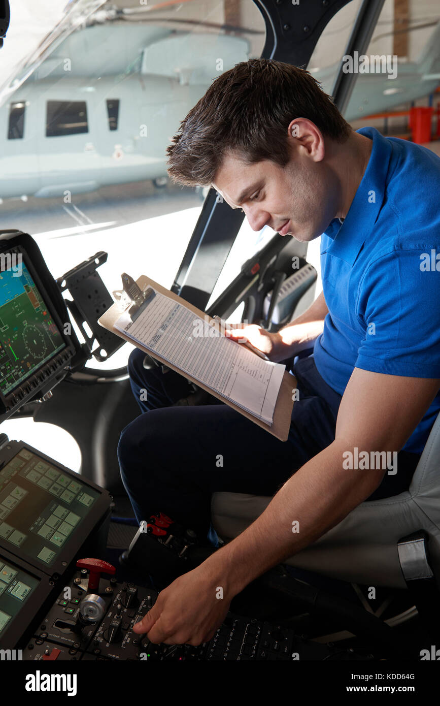 Male Aero Engineer With Clipboard Working In Helicopter Cockpit - Stock Image