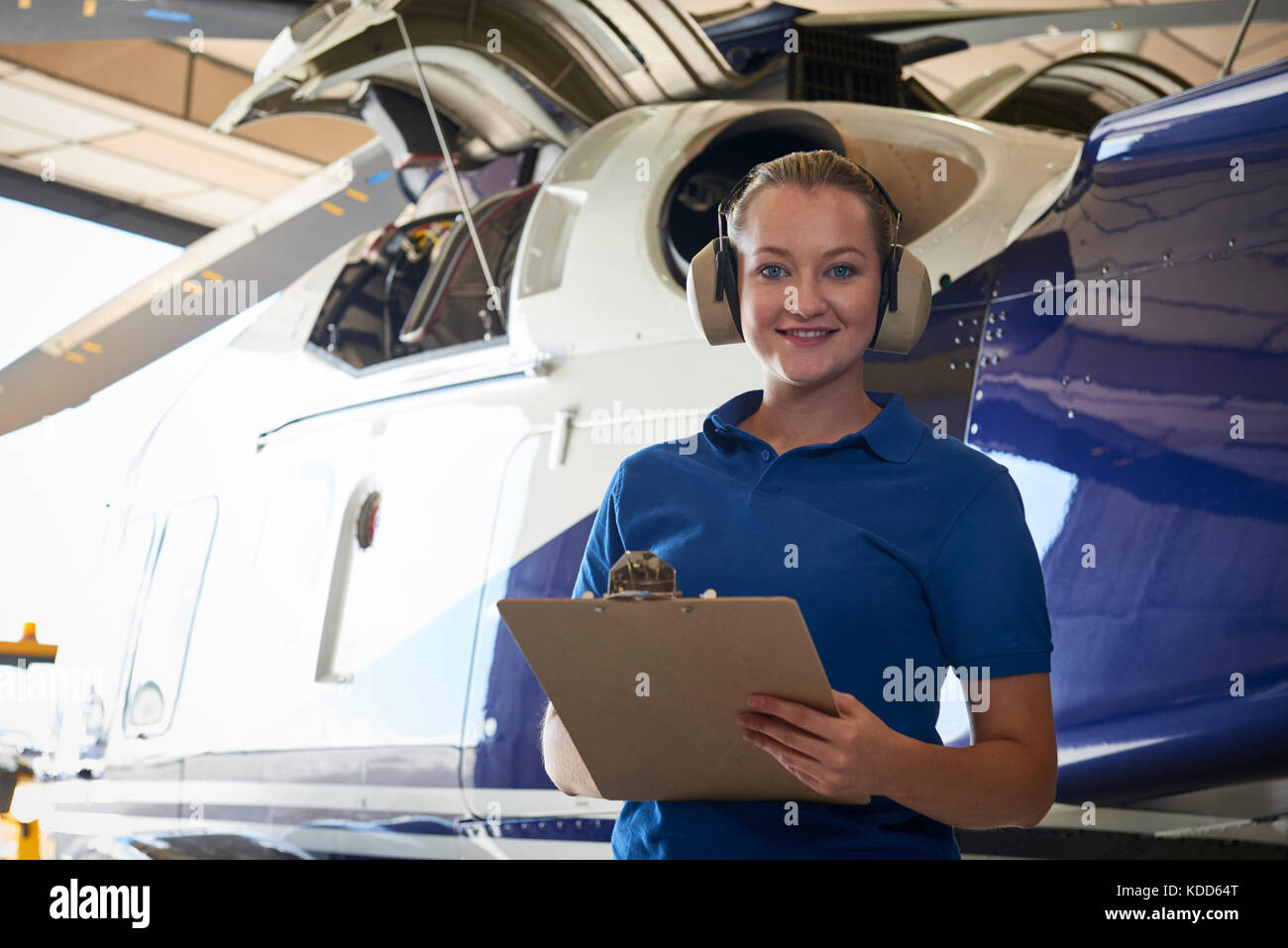 Portrait Of Female Aero Engineer With Clipboard Carrying Out Check On Helicopter In Hangar - Stock Image