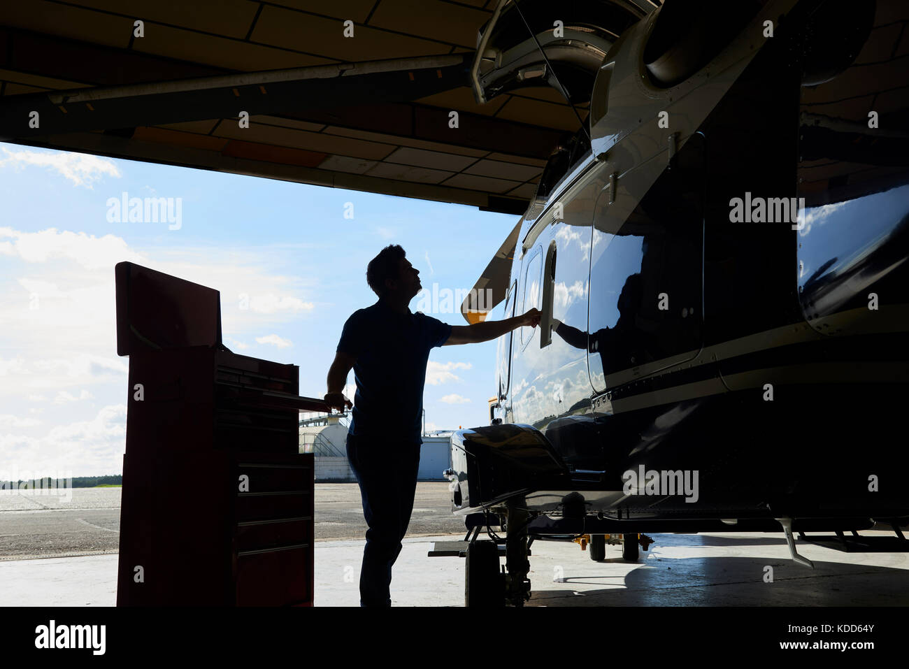 Silhouette Of Male Aero Engineer Working On Helicopter In Hangar - Stock Image