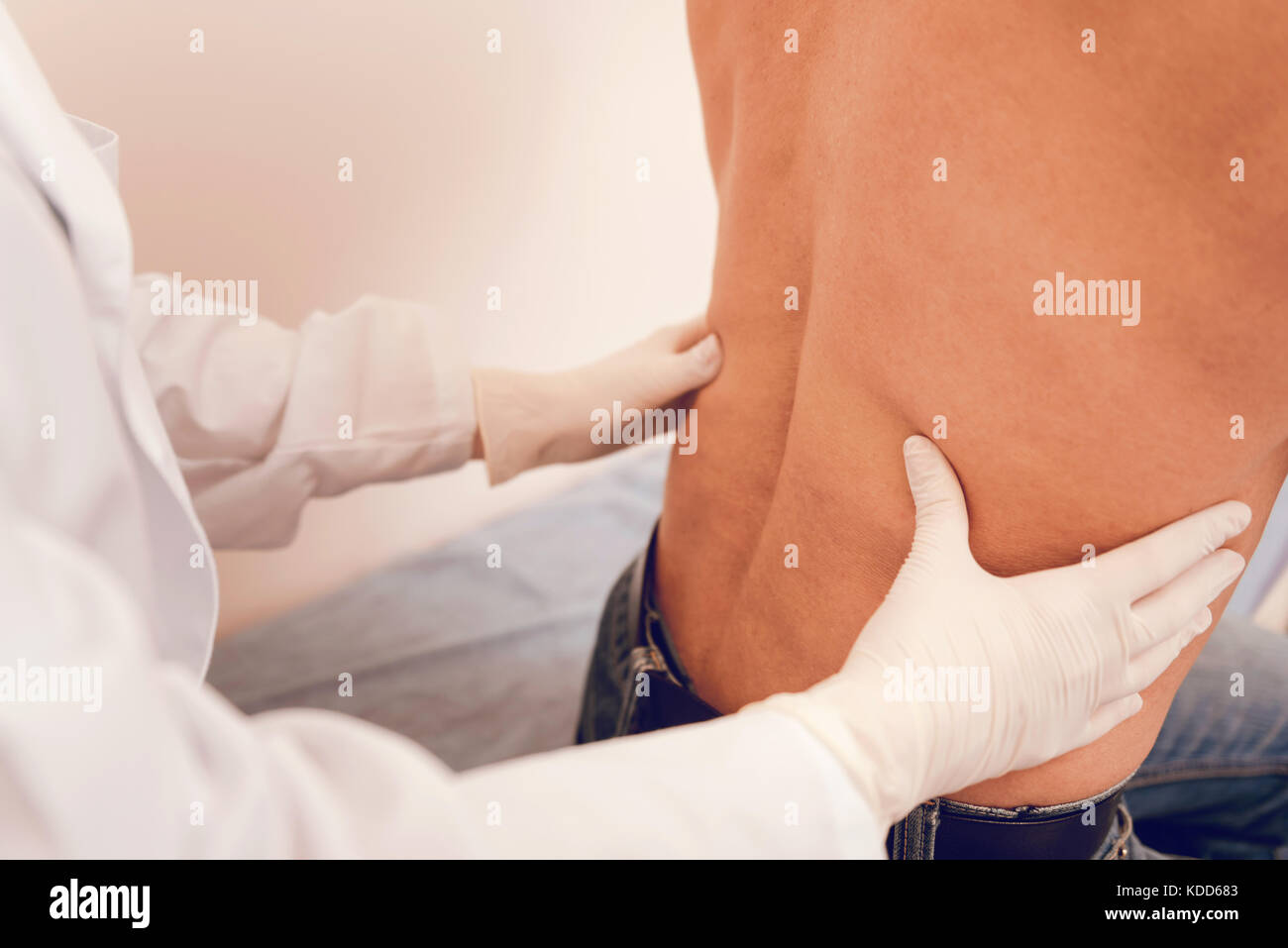 Competent doctor putting hands on male body - Stock Image