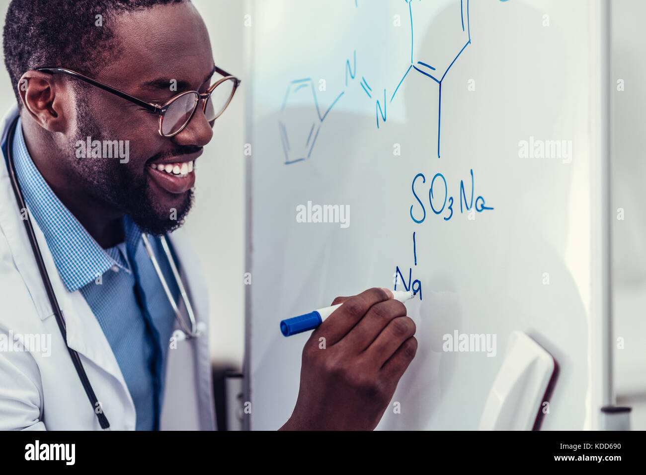 Excited African American medical worker drawing chemical drawing - Stock Image